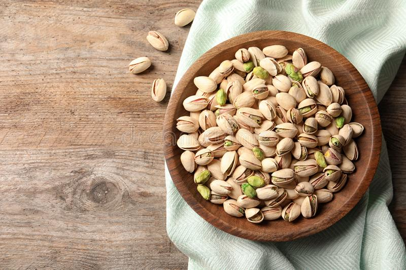 Organic pistachio nuts in bowl on wooden table, top view. Space for text royalty free stock photo