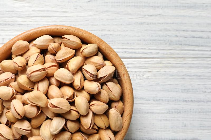 Organic pistachio nuts in bowl on wooden table, top view. Space for text royalty free stock photography