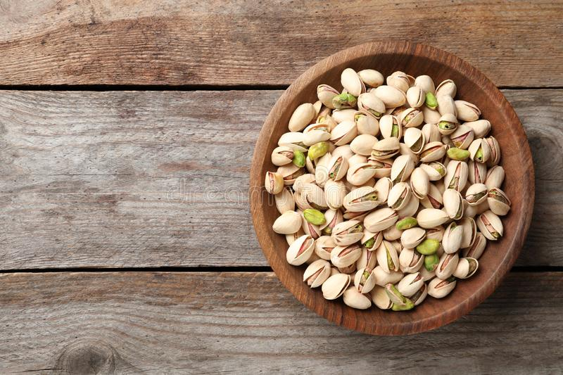Organic pistachio nuts in bowl on wooden table, top view. Space for text royalty free stock images