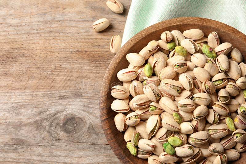 Organic pistachio nuts in bowl on wooden table, top view stock images