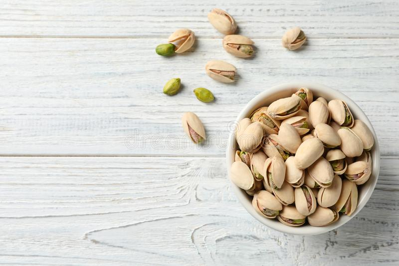 Organic pistachio nuts in bowl on wooden table, top view royalty free stock images