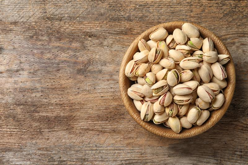 Organic pistachio nuts in bowl on wooden table, top view. stock photos