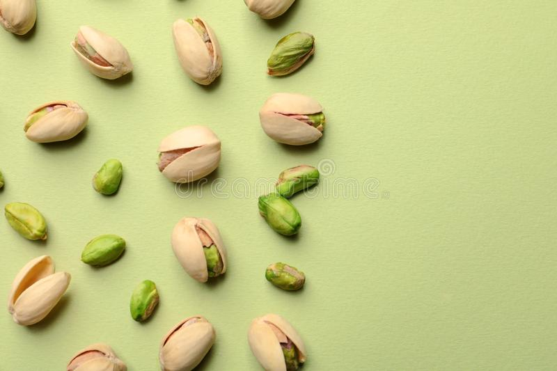 Organic pistachio nuts on color background. Space for text. Organic pistachio nuts on color background, flat lay. Space for text royalty free stock photography