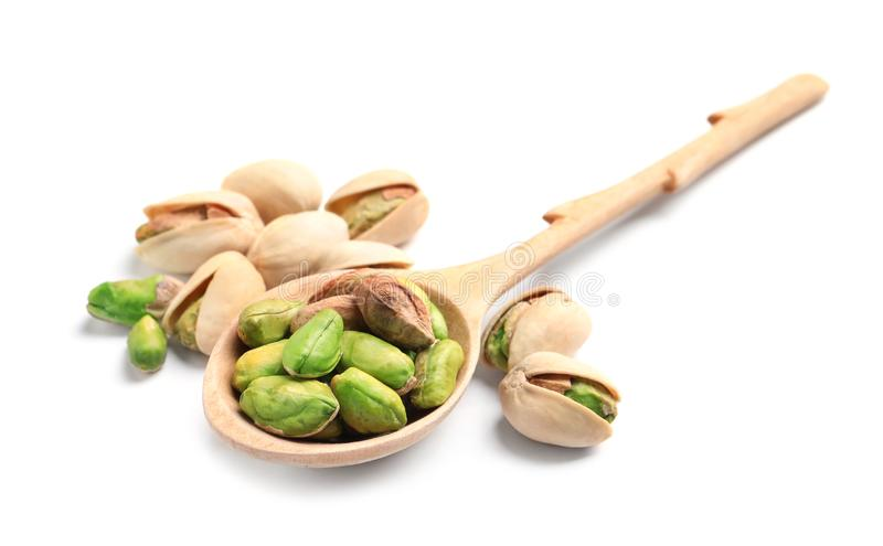 Organic pistachio nuts and spoon on white background. Closeup royalty free stock photo