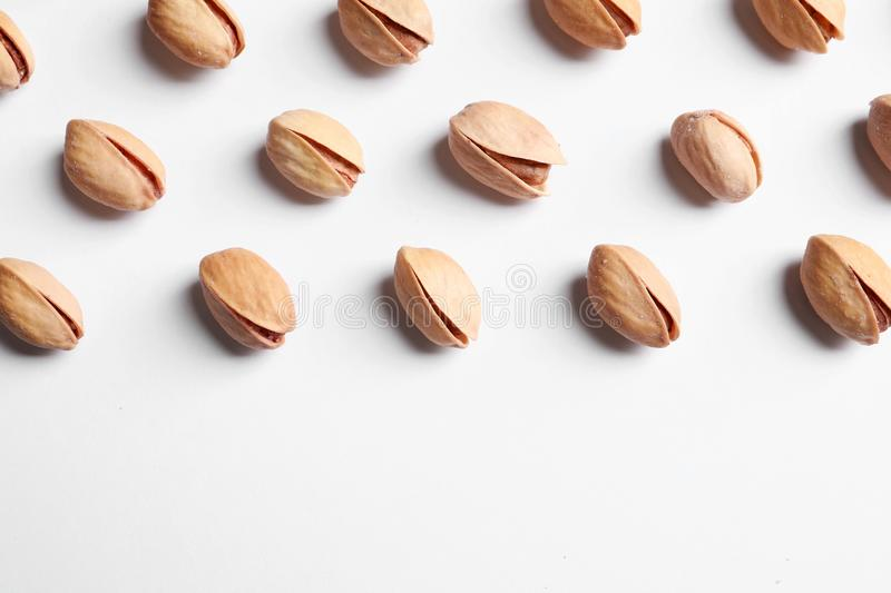 Organic pistachio nuts on white background, flat lay. stock images