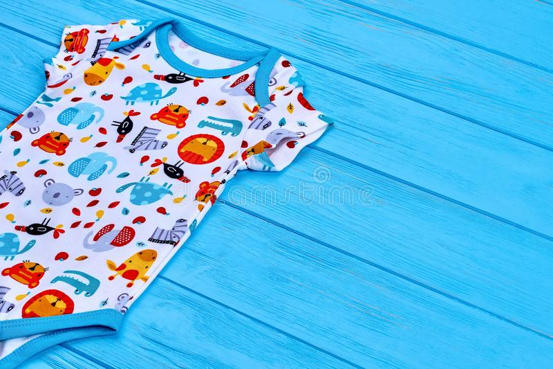 Organic printed bodysuit for newborn. Toddler summer jumpsuit on blue wooden background. Infant baby summer apparel royalty free stock photography