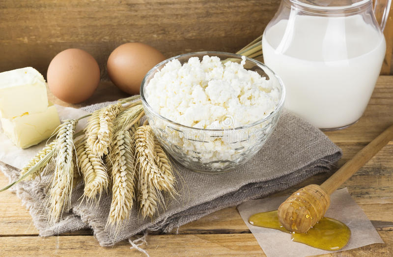 Organic products: eggs, milk, cottage cheese, honey, butter, wheat on a wooden background royalty free stock photo