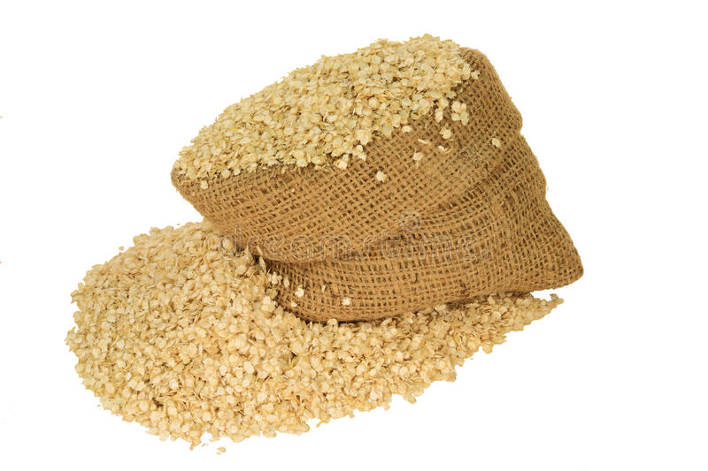 Organic Quinoa Flakes. Processed to Flakes Organic Quinoa seeds in burlap bag and spilled out on pile isolated over white background royalty free stock photos