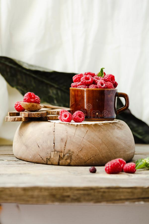 Organic raspberry with basil in a cup of coffee and a wooden sta royalty free stock photos