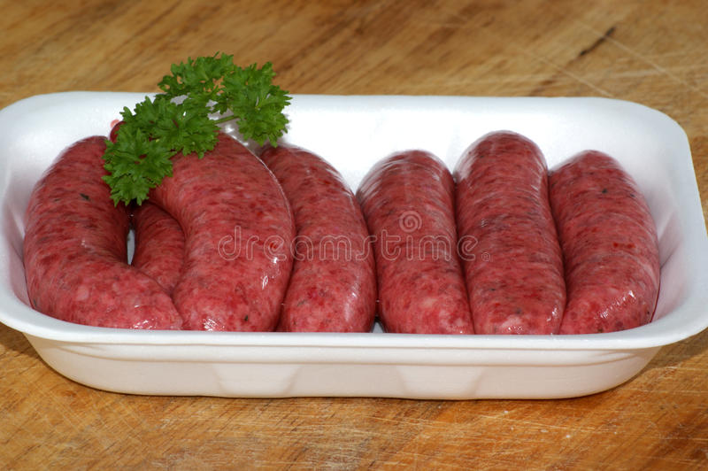 organic raw beef sausages and parsley stock images