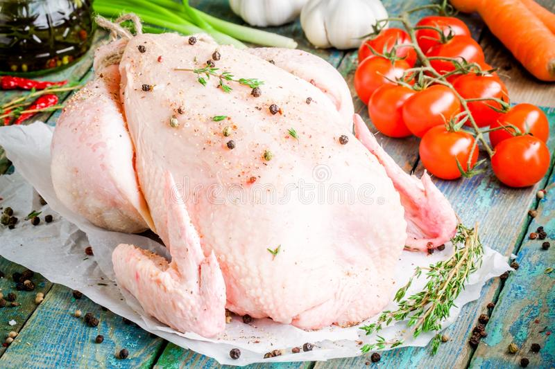 Organic raw chicken with thyme, pepper, tomatoes, carrots on a rustic table stock image