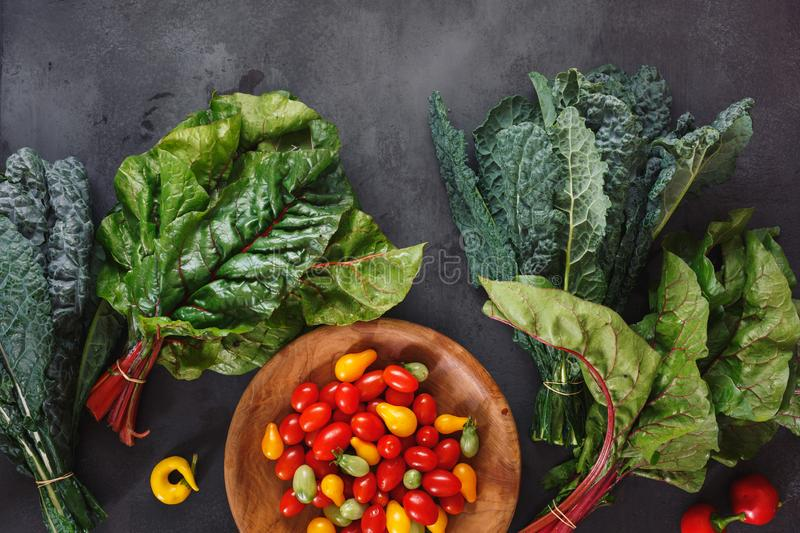 Organic raw  mixed fresh greens, tomatoes and chili from the farmers market royalty free stock photo