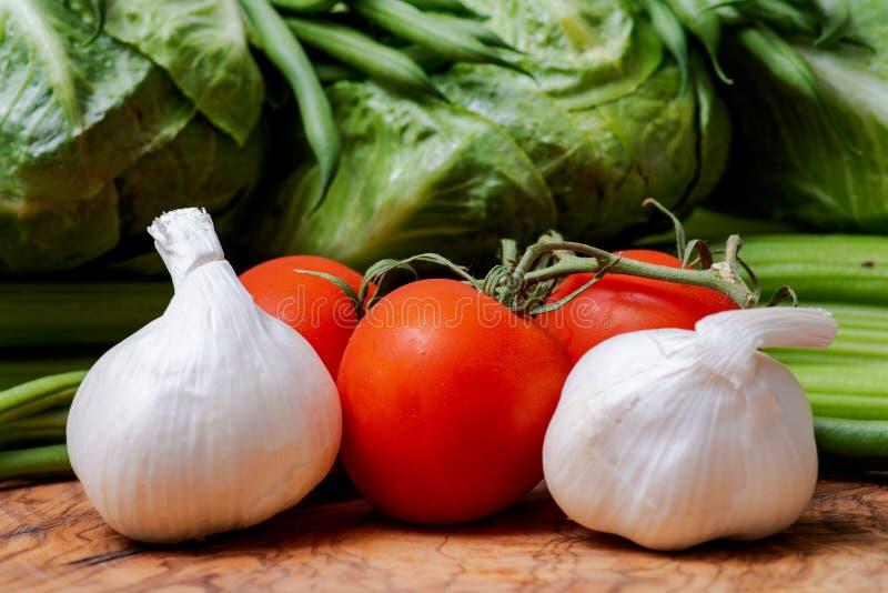 Organic Raw Whole Garlic bulbs and  Red Tomatoes on the vine arranged on olive wood. Allium sativum. Solanum lycopersicum. royalty free stock photo