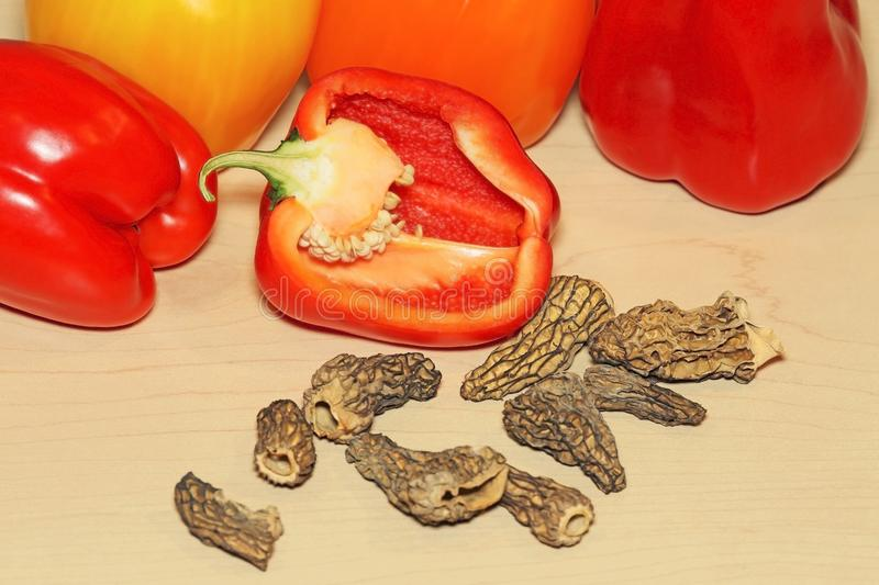 Organic Bell Peppers and tried Morel Mushrooms on maple Wood board stock images