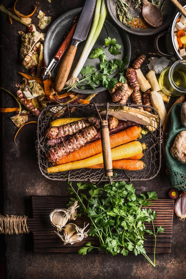 Organic root vegetables in harvest basket on dark rustic kitchen table background with ingredients for tasty cooking with greens stock photography