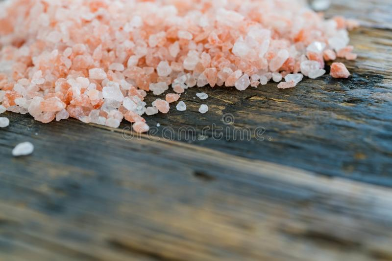 Organic rose pink himalaya salt crystals on rustic wooden table. Close up horizontal view of rose pink organic himalaya salt crystals on a rustic wooden table royalty free stock photography