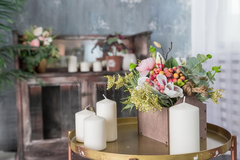 Organic candle on table. Loft interior decor, minimalism concept. Closeup, eco home decor with green leaves, flowers and. Organic scented soy candle on grey stock photography