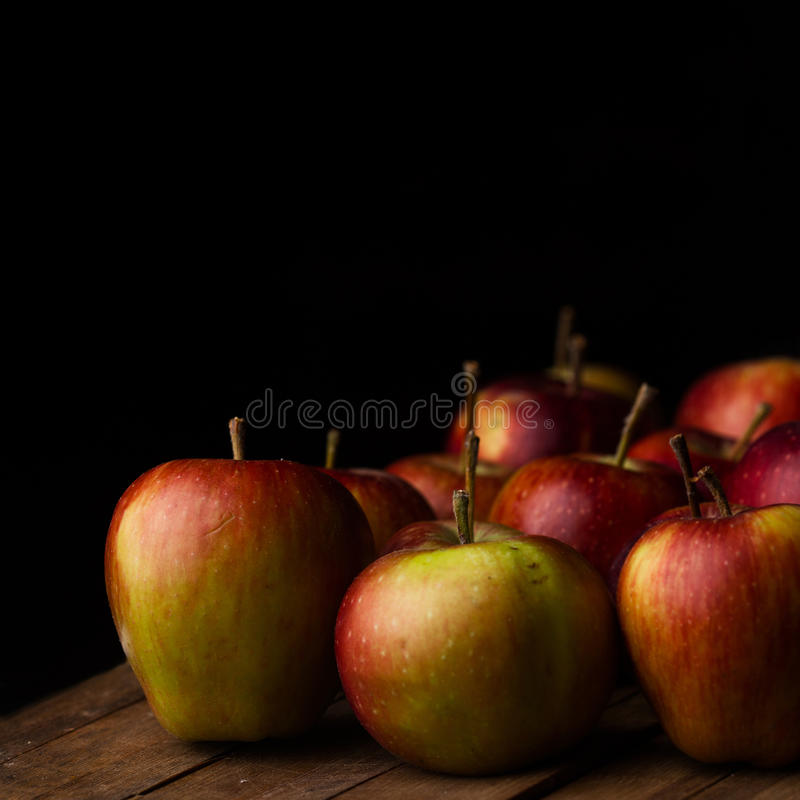 Organic small garden ripe apples on wooden plank. Front view of organic small red apples vintage wood board with black background stock image
