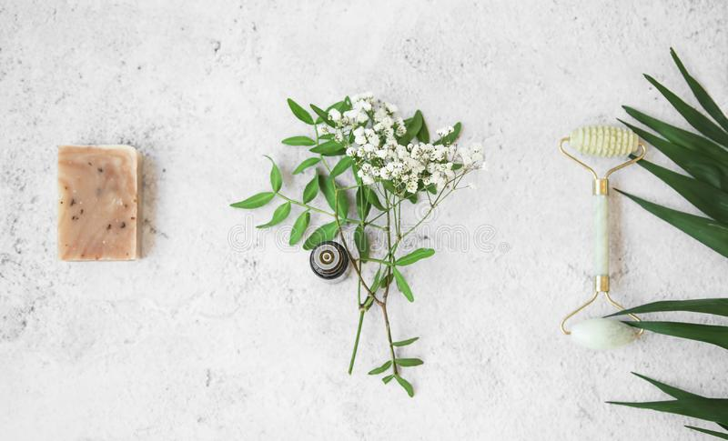 Organic spa. natural herbal skincare ingredients with herbs and plants, natural soap, essential oil, jade face roller,top view stock photography