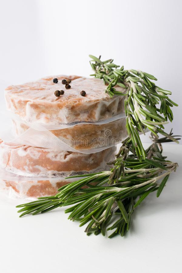 Organic stack of fresh raw burger patty and pepper isolated on white. Raw Minced burger Meat with rosemary Herb and black pepper in glass jar Prepared for stock photos