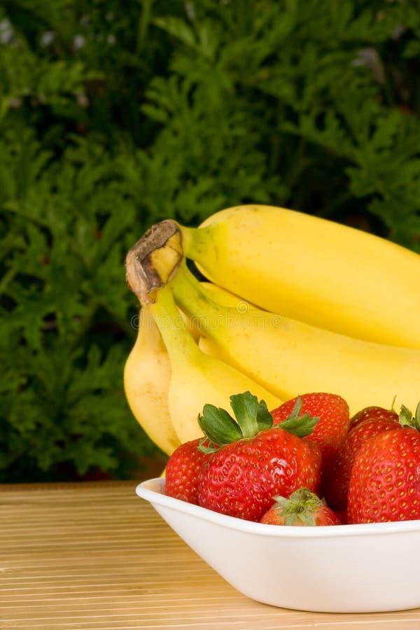 Organic strawberries and bananas stock photography