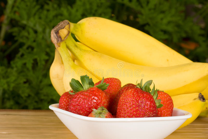 Organic strawberries and bananas. Organic strawberries in a white bowl with a bunch of organic bananas behind. selective focus on the strawberries royalty free stock image