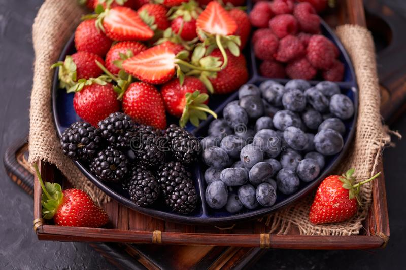 Organic strawberries, raspberries, blueberries, blackberries on a separate dish close-up on a solid concrete background. Healthy eating Vegan food. High Diet royalty free stock photography