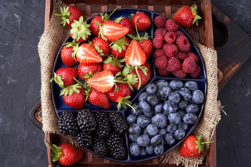 Organic strawberries, raspberries, blueberries, blackberries on a separate dish close-up on a solid concrete background. Healthy eating Vegan food. High Diet royalty free stock images