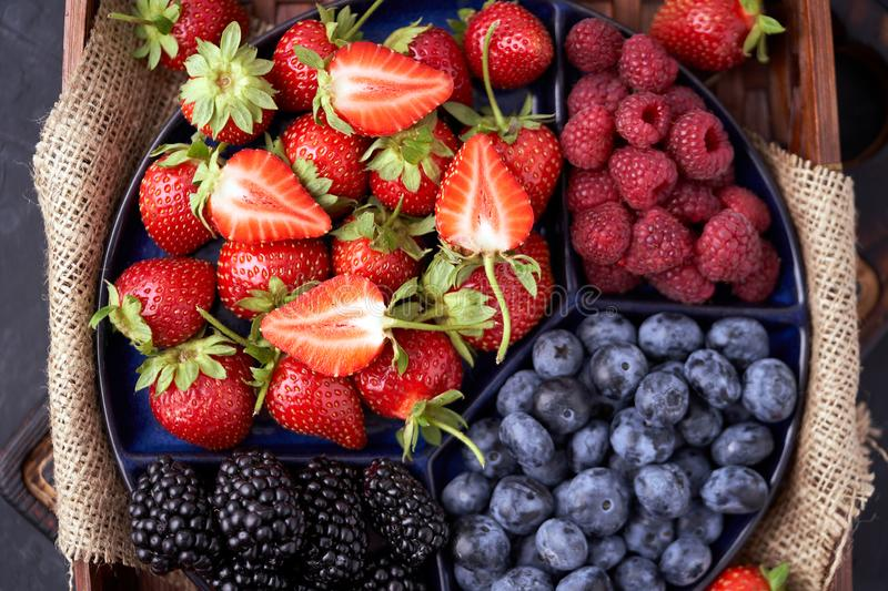 Organic strawberries, raspberries, blueberries, blackberries on a separate dish close-up on a solid concrete background. Healthy eating Vegan food. High Diet royalty free stock photo
