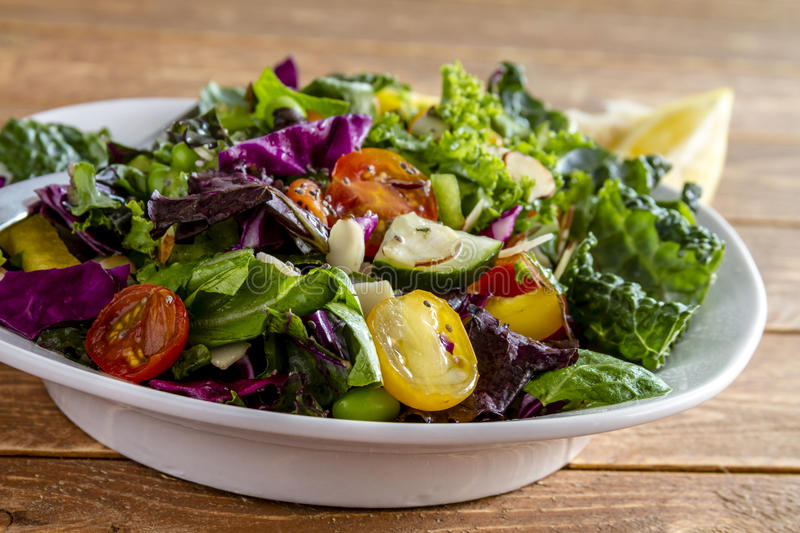 Organic Super Food Vegetarian Salad. Close up of fresh organic super food salad in white bowl sitting on wooden table royalty free stock photos