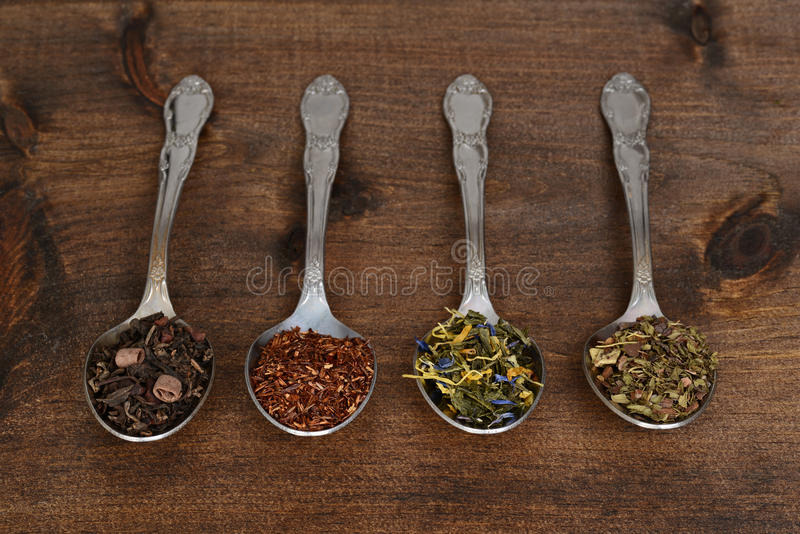 Organic tea on spoons. On wood table royalty free stock images