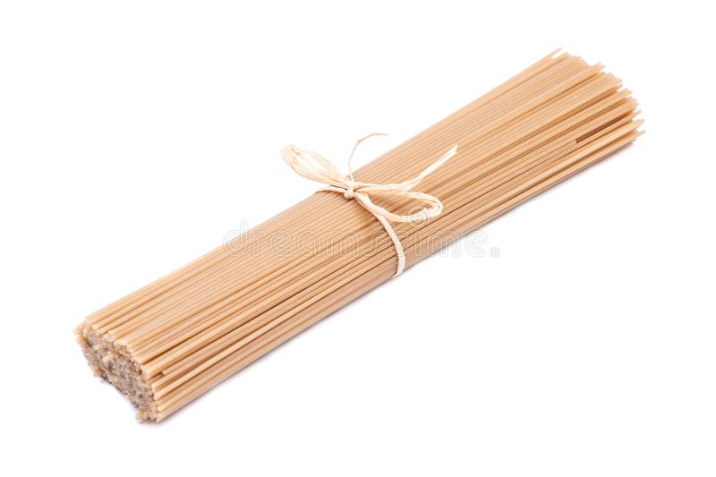 Organic uncooked Brown Rice Spaghetti pasta tied with a straw isolated on white background. Gluten-free and sodium-free royalty free stock image