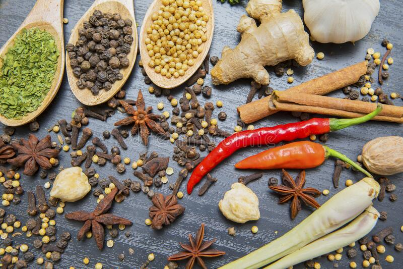 Organic various herbs and spices in wooden spoons royalty free stock photo