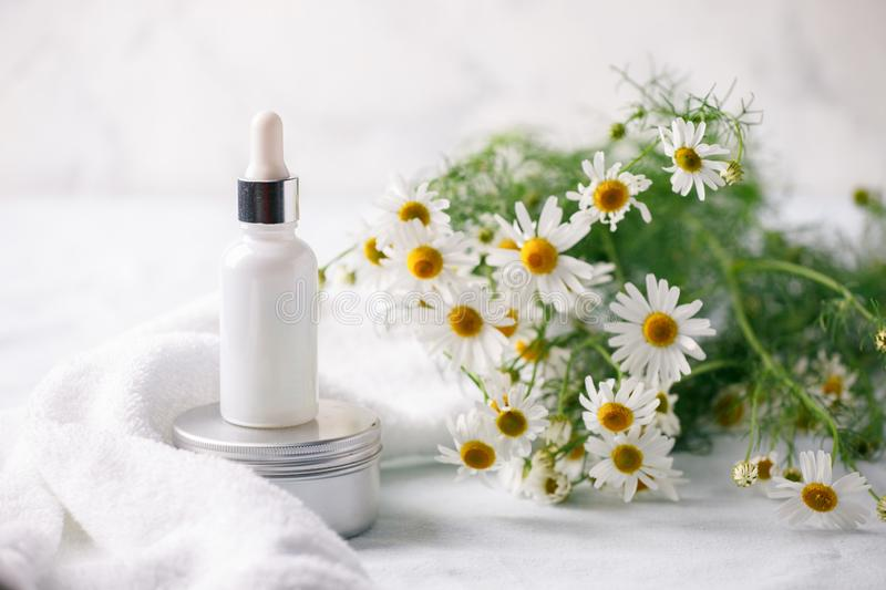 Organic vegan natural cosmetics concept. Chamomile flowers and cosmetic bottles of cream and serum essential on white background. Zero waste cosmetic package stock images
