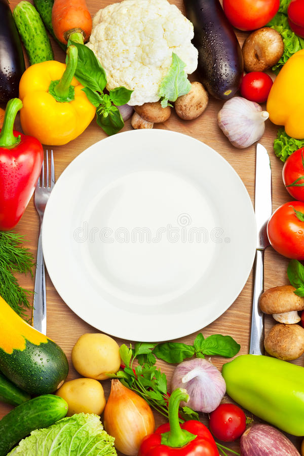 Free Organic Vegetables Around White Plate With Knife And Fork Royalty Free Stock Photo - 35169525