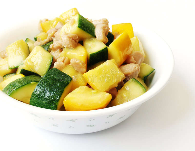 Organic zucchini & chicken stir fry dish. A simple yet tasty dish of stir fried yellow and green organic zucchinis with small pieces of marinated chicken. Served royalty free stock photography