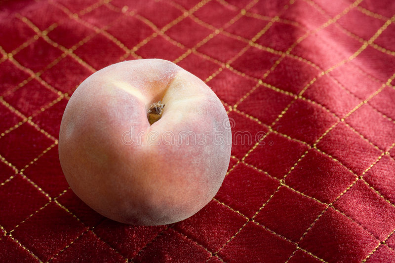 Organically Grown Peach On Red Tablecloth Royalty Free Stock Photography