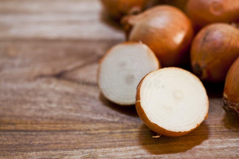 Organicznie świeże cebule usypują zbliżenie na nieociosanym drewnianym stołowym tle zdjęcia stock