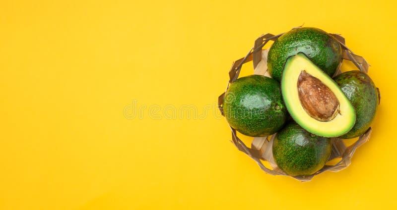 Organicznie avocados połówki cięcie z nasieniodajną i całą owoc w koszu na koloru żółtego stołu tle Zdrowi super foods dla diety  zdjęcia royalty free