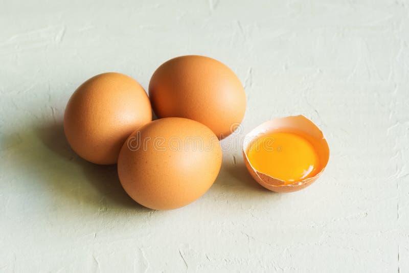 Organicznie cali i krakingowi bezpłatni pasma brązu jajka z jaskrawym pogodnym glansowanym yolk na szarość drylują tło Kulinarny  obraz royalty free