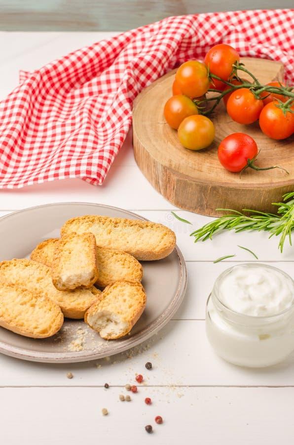Organicznie czereśniowi pomidory z rozmarynami, szwedzi grzankami i śmietanką, zdjęcie stock
