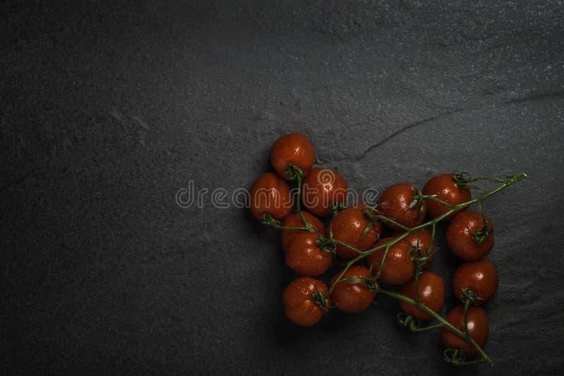 Organicznie dojrzałego mini Roma winogradu czereśniowi pomidory na zmroku drylują tło obrazy stock