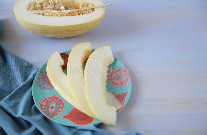 Organicznie dojrzały żółty słodkiego melonu cięcie w połówce i plasterki na białym błękitnym tle obrazy royalty free