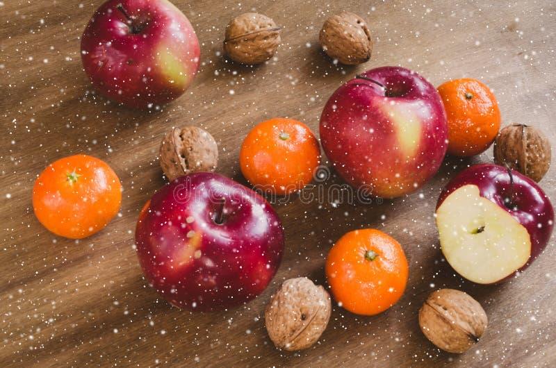 Organicznie jabłka, tangerines i orzechy włoscy na drewnianym tle, obraz stock