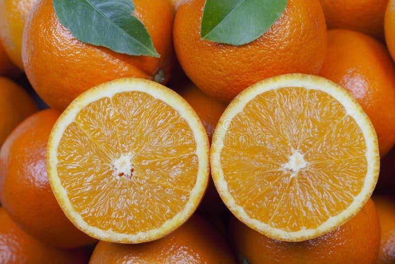 Organicznie pomarańcze z jeden cięciem w połówce na wierzchołku zdjęcie stock