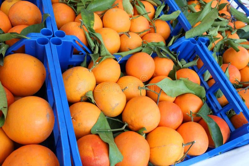 organicznie pomarańcze z liśćmi w owoc boksują na sprzedaży obrazy stock