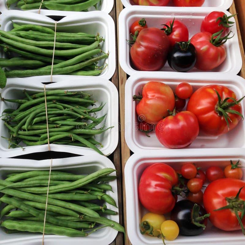 Organicznie pomidory i zielone francuskie fasole w compostable pakować obraz royalty free