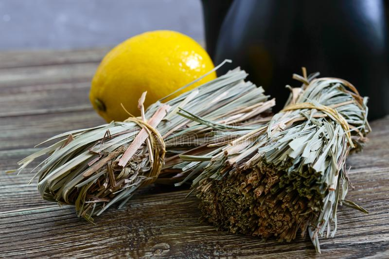 Organicznie suchy lemongrass Cymbopogon flexuosus w wiązkach i cytryny owoc na drewnianym stole Ziele dla herbaty zdjęcia stock