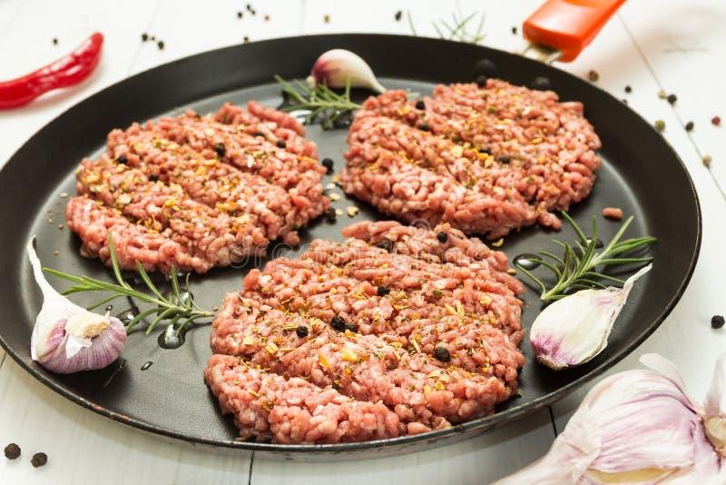 Organicznie wołowiny surowi cutlets z pikantność w smaży niecce na białym tle z czosnkiem, rozmarynami i pieprzem, obraz royalty free