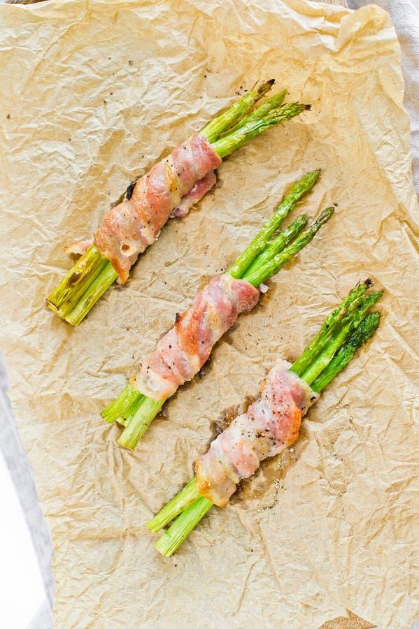 Organicznie zielony mini asparagus zawijaj?cy w bekonie na drewnianej tn?cej desce Bia?y t?o, odg?rny widok obrazy stock